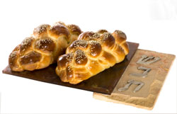 challah on a cutting board with Shabbat on it in Hebrew