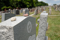 headstones at a Jewish cemetery with rocks left by visitors