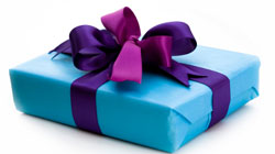 wrapped gift in blue paper with purple ribbon