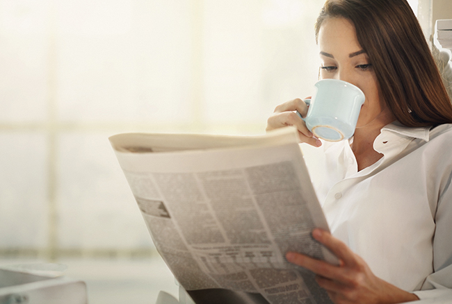 Woman having coffee and reading newspaper. Taking a quiet moment.