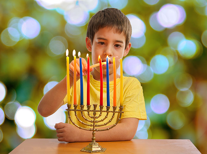 Boy lighting Hanukkah menorah