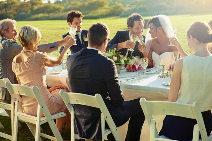 Bride and groom with guests toasting at wedding reception.