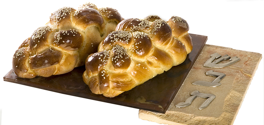 Two freshly-baked loaves of braided challah bread on a unique stained glass/stone cutting board.