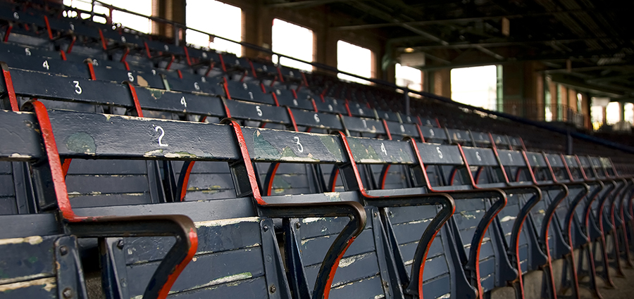 A group of old stadium seats with an awning in the background.