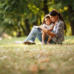 Mother and daughter reading a book in the park