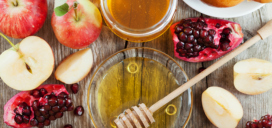 Rosh Hashanah, Jewish New Year Holiday, Honey, apple, pomegranate, challah on a wooden table