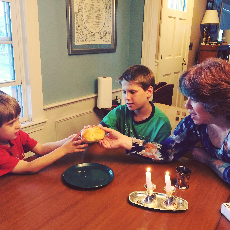 Family blesses the challah for Shabbat