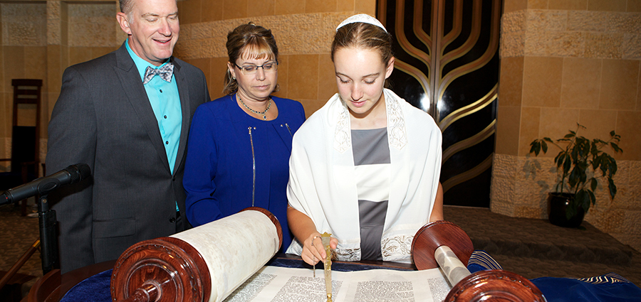 Girl Reading Torah with her parents