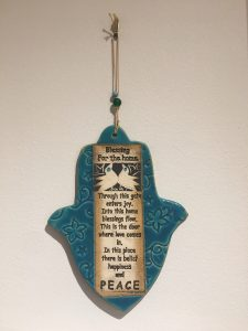 Hamsa with script: Blessing for the home. Through this gate enters joy. Into this home blessings flow. This is the door where love comes in. In this place there is belief happiness and peace