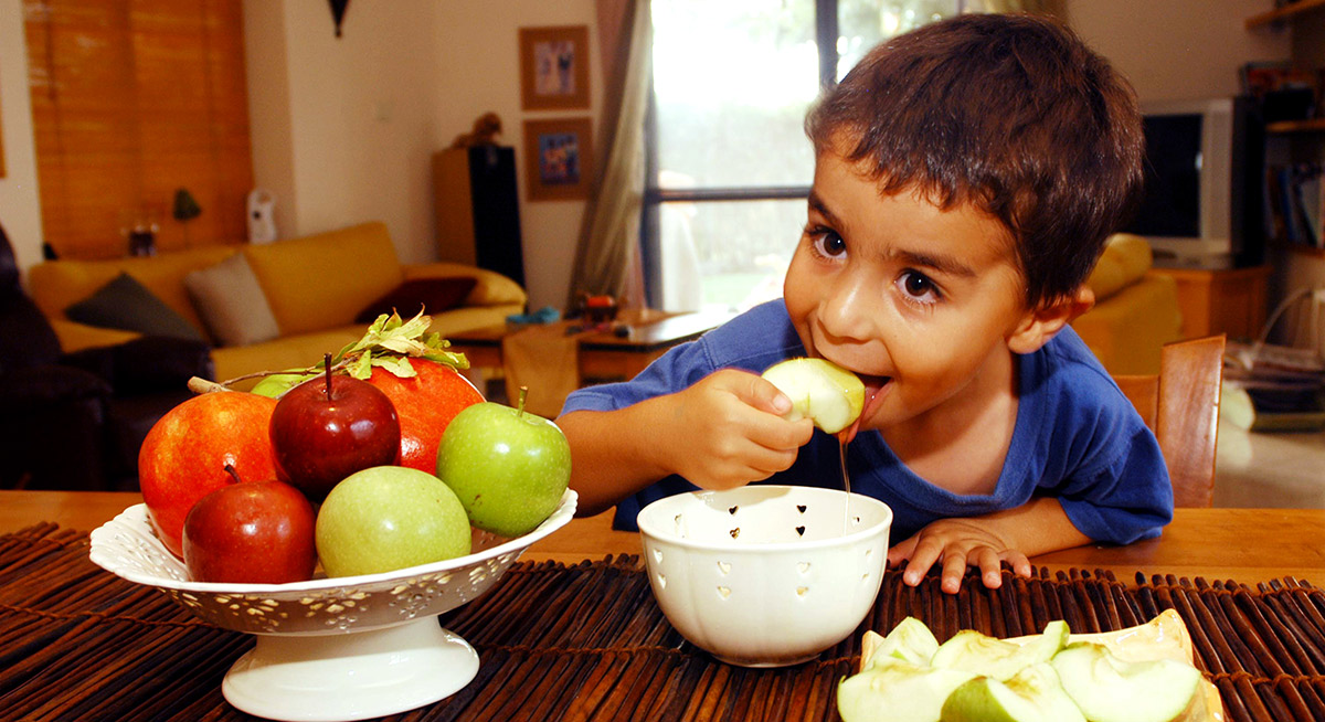 child eating apples and honey