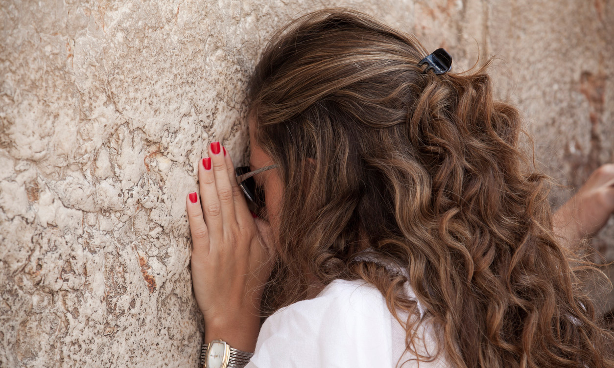 Woman praying at Western wall